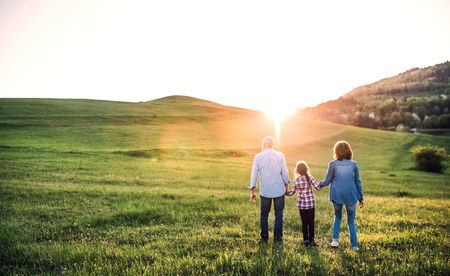 Senior couple with granddaughter outside in spring nature, walking at sunset.