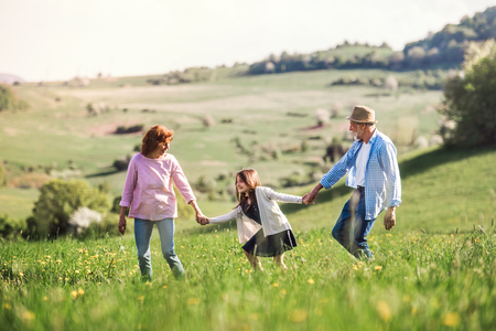 Senior couple with granddaughter outside in spring nature.