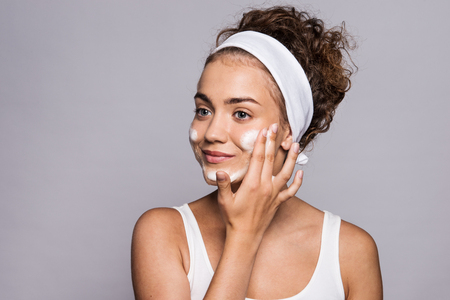 Portrait of a young woman cleaning face in a studio, beauty and skin care.