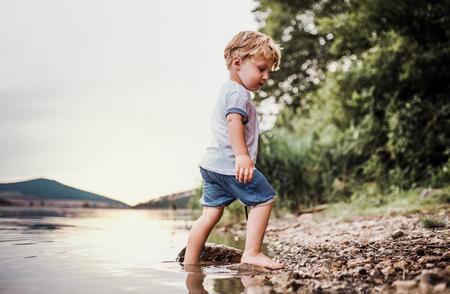 Ein nasser, kleiner Kleinkindjunge, der im Sommer draußen in einem Fluss steht und spielt.