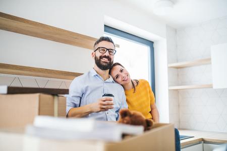Una giovane coppia che beve caffè quando si trasferisce in una nuova casa. Archivio Fotografico