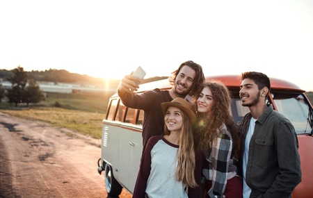 A group of young friends on a roadtrip through countryside, taking selfie. Reklamní fotografie