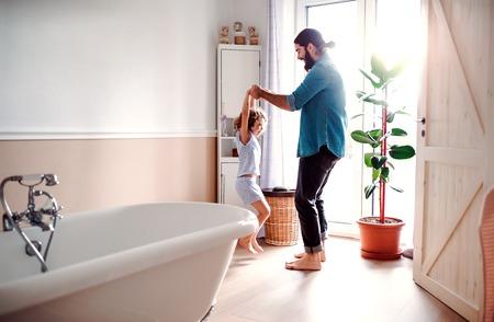 Petite fille avec jeune père dans la salle de bain à la maison, s'amusant.