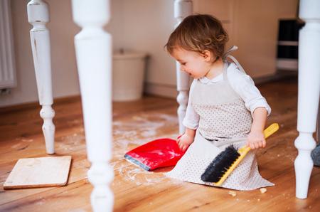Una niña pequeña con cepillo y recogedor de piso de barrido en la cocina de casa. Foto de archivo