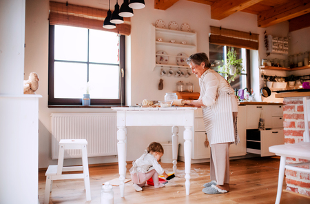 Senior grandmother with small toddler grandchild making cakes at home. Stockfoto