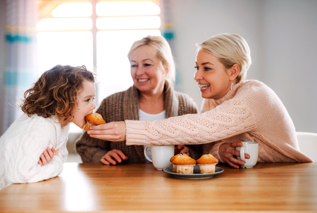 A portrait of small girl with mother and grandmother at the table at home. Stockfoto - 120798179