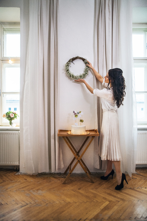 A woman hanging up a wreath on wall on indoor party, a cake on stand. Stockfoto