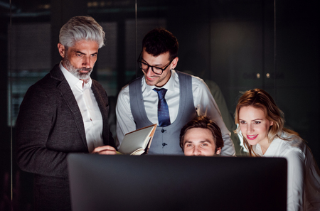 A group of business people in an office at night, using computer. Stock Photo