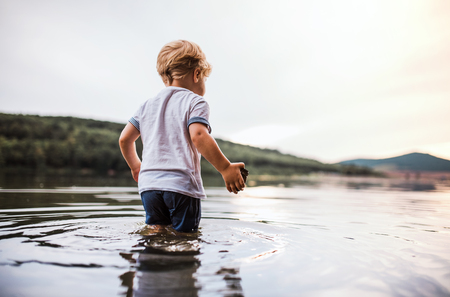 A wet, small toddler boy walking outdoors in a river in summer, playing.