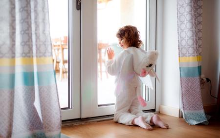 Ein kleines Mädchen in Einhornmaske, das zu Hause spielt.