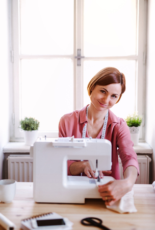 Young creative woman in a studio, working. A startup of tailoring business. Stock Photo