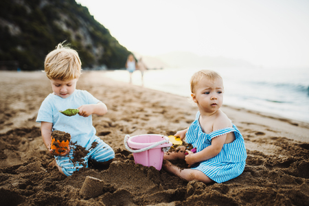 Two toddler children playing on sand beach on summer holiday.