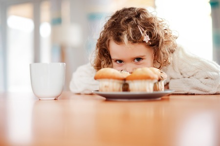 A portrait of small girl with muffins sitting at the table at home. Stockfoto - 121218918