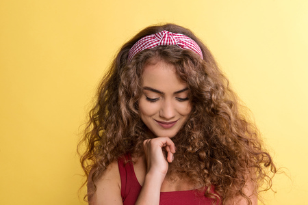 Portrait of a young woman with headband in a studio on a yellow background. 免版税图像