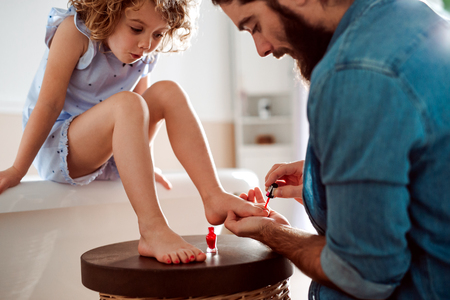 Young father painting small daughters nails in a bathroom at home.