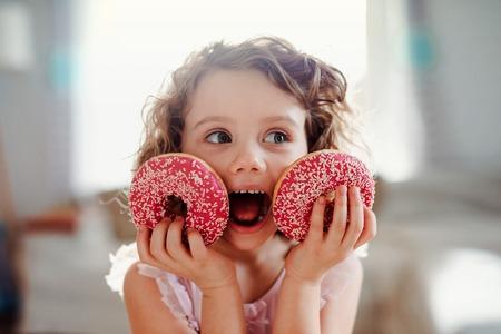 Een klein meisje met donuts thuis, camera kijken.