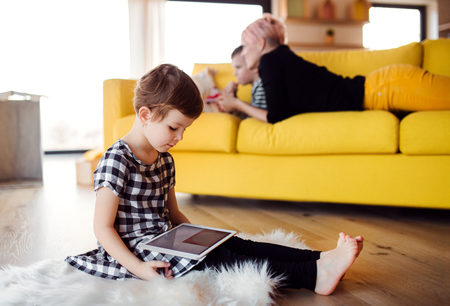 A small girl using tablet indoors on the floor at home.
