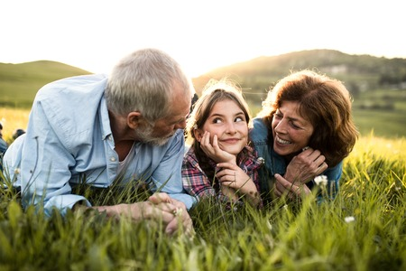 Senior couple with granddaughter outside in spring nature, relaxing on the grass.