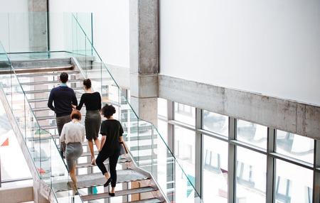 Rückansicht einer Gruppe junger Geschäftsleute, die die Treppe hinaufgehen.