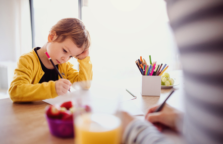 Unrecognizable mother with small daughter drawing in a kitchen.