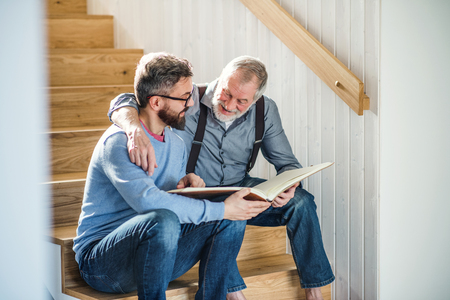An adult son and senior father sitting on stairs indoors at home, looking at photographs.