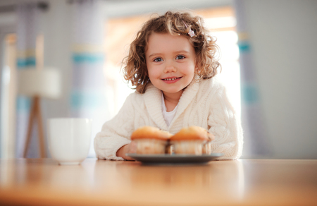 A portrait of small girl with muffins sitting at the table at home.
