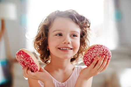 A small girl with doughnuts at home, having fun. Reklamní fotografie