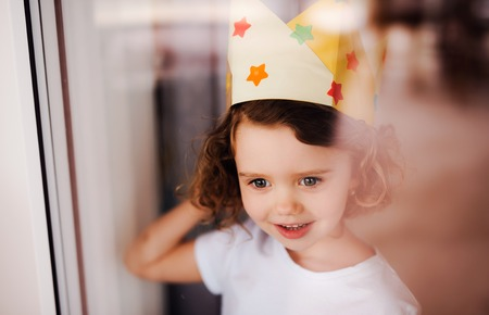 Portrait of small girl with crown at home, looking out of a window. Shot through glass.