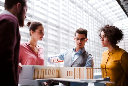 Group of young architects with model of a house standing in office, talking.