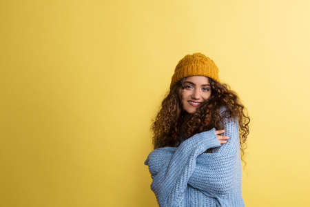 Portrait of a young woman with woolen hat in a studio on a yellow background.
