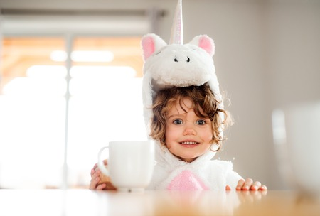 A portrait of small girl in unicorn mask sitting at the table at home. 스톡 콘텐츠
