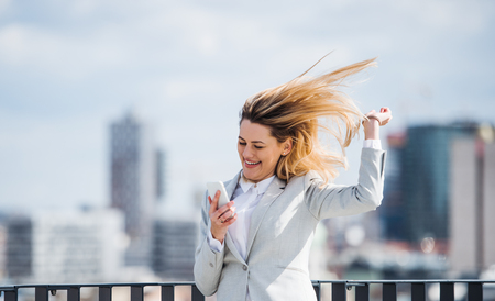 A young businesswoman with smartphone standing on a terrace, expressing excitement.