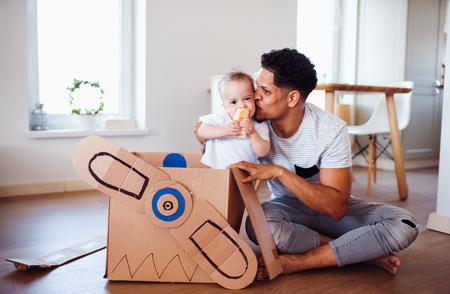 Père et petit fils à l'intérieur à la maison, jouant. Banque d'images