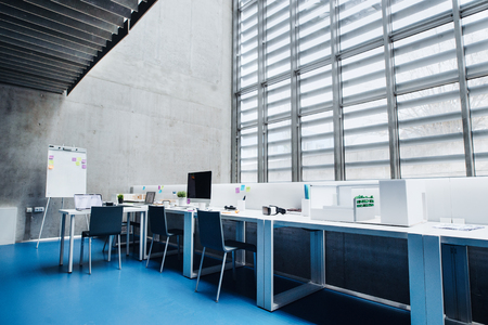 An interior of desks with computer in modern spacious office.