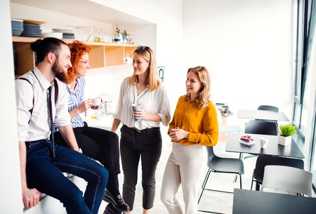 A group of young business people on coffee break in office kitchen.