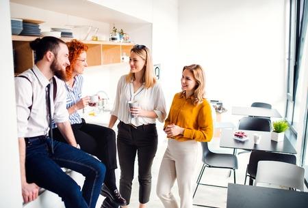 Eine Gruppe junger Geschäftsleute in der Kaffeepause in der Büroküche.