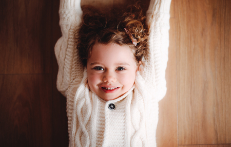 A portrait of small girl with white knitted sweater lying on the floor, a top view. Stockfoto