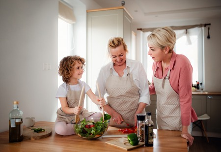 A small girl with mother and grandmother at home, preparing vegetable salad.