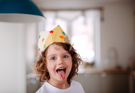 A small girl with a paper crown at home, having fun when looking at camera.
