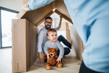 A portrait of young family with a toddler girl, moving in new home concept.