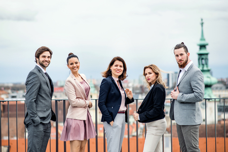 A group of joyful businesspeople standing outdoors on roof terrace in city. Фото со стока - 122628495