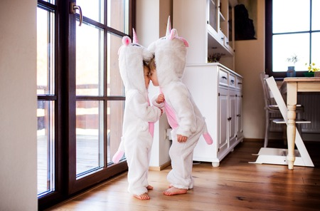 Two toddler children with unicorn masks playing indoors at home.