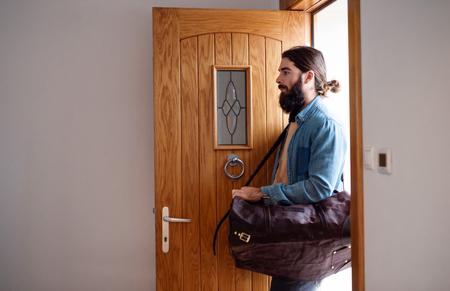 Hombre joven inconformista con bolsa entrando por la puerta de entrada al volver a casa.