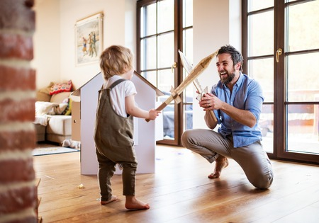 A toddler boy and father with carton swords playing indoors at home.