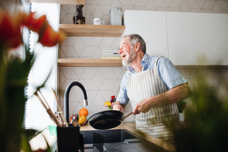 A senior man indoors in kitchen at home, washing up a pan. Foto de archivo - 122964277