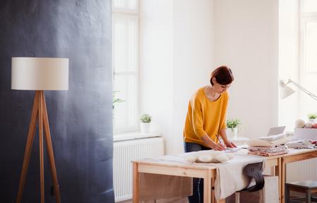 Junge kreative Frau in einem Studio, Start eines kleinen Schneidergeschäfts.
