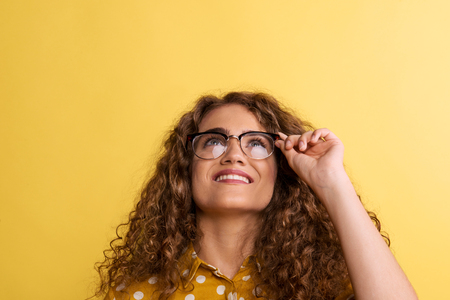 Portrait of a young woman with glasses in a studio on a yellow background. Stok Fotoğraf