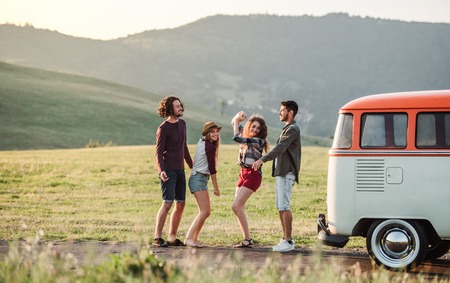 A group of friends standing outdoors on a roadtrip through countryside, dancing.