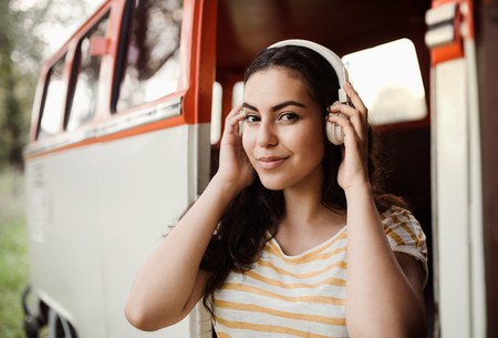 A young girl with headphones on a roadtrip through countryside, listening to music. Stockfoto