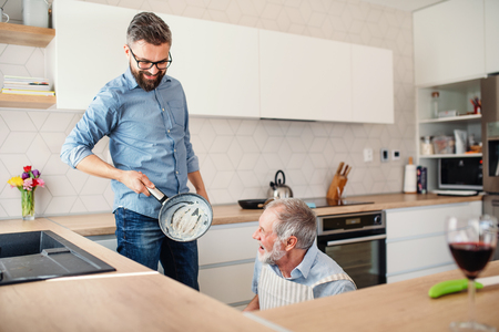 Adult hipster son and senior father indoors in kitchen at home, cooking. 版權商用圖片